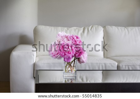 vase of pink peony flowers with white living room furniture - stock photo