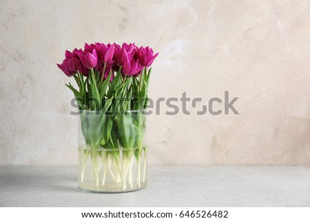 Vase with beautiful tulips on table