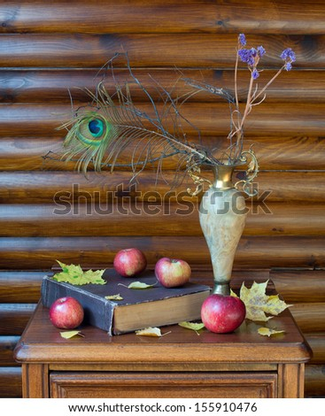 Vase with dried twigs and peacock feather, old book, apples and autumn leaves on wooden table - stock photo