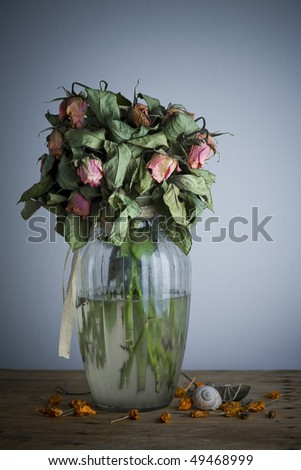 vase with old roses on the wooden table