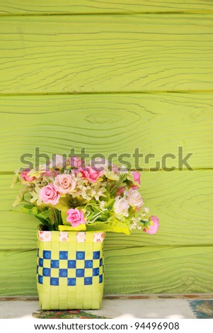 Vase with Plastic flowers and green wall - stock photo