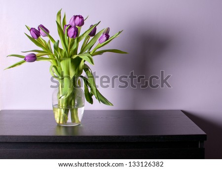 Vase with purple tulips on black table with lilac walls - stock photo