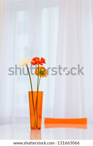 Vase with three gerbera flowers on the table in dining area - stock photo
