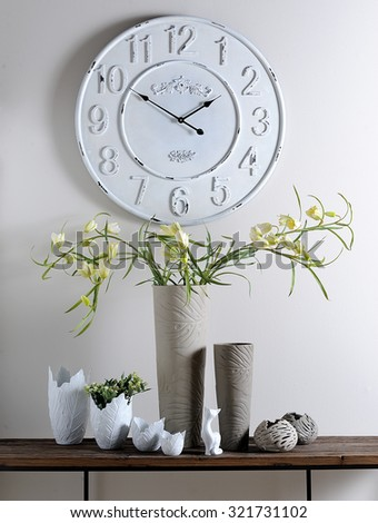vases - the one with flowers- and clock in a composition in a decorative spot on a showroom - stock photo