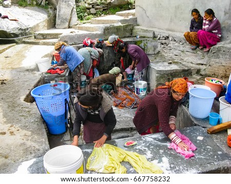 VASISHTA VILLAGE, CITY OF MANALY, STATE HIMACHAL PRADESH, INDIA - APRIL 18, 2014: Women wash clothes at the source. in a small village in the Himalayas in the north of the state Himachal Pradesh.