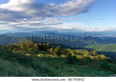 Vast landscape view over a meadow and several mountains