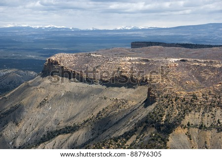 Vast view of a mesa and distant snow-capped mountains from and overlook in Mesa Verde National Park.