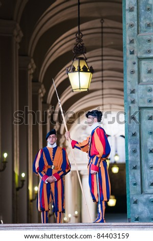 VATICAN - AUGUST 30: Unidentified papal Swiss guards stands at a non-public door of the Vatican Museum on August 30, 2011 in the Vatican. The Swiss guards served since the late 15th century.