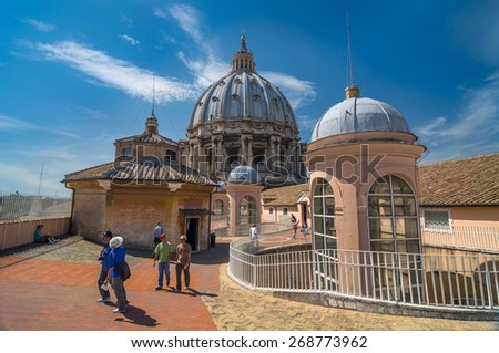 VATICAN CITY, ITALY - APRIL 16, 2013: Tourists walk on the top of St Peter Basilica roof. The dome with column and arch. Vatican City, Rome, Italy - stock photo
