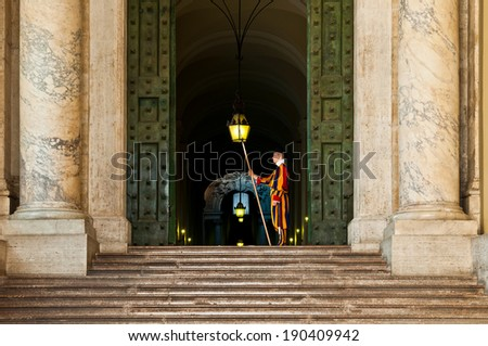 VATICAN CITY - SEPTEMBER 21: unidentified Papal Swiss guard standing at the Vatican Museums door on September 21, 2013 in the Vatican. The Swiss guards served since the late 15th century. - stock photo