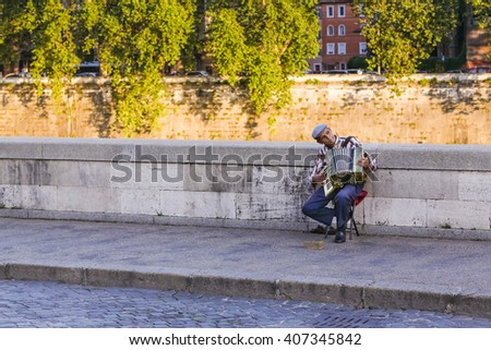 Vatican, Italy - June 26, 2014: A street musician playing the accordion near Saint Angel Bridge in Italy. - stock photo
