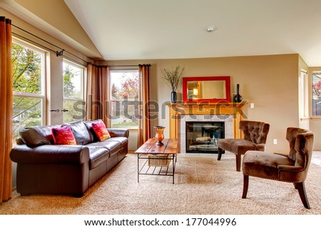 Vaulted ceiling living room with soft carpet floor and cozy fireplace. Furnished with leather couch, antique style chairs and rustic wooden coffee table - stock photo
