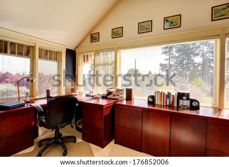 Vaulted ceiling office room with carpet floor, bright cherry cabinets, black whirpool chair - stock photo