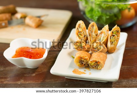 Veg. Spring Rolls, on white dish and wooden table / Selective focus
