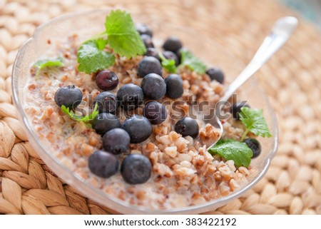 Vegan buckwheat porridge topped with organic blueberries and fresh mint in a glass plate on a straw table mat. Healthy breakfast  - stock photo