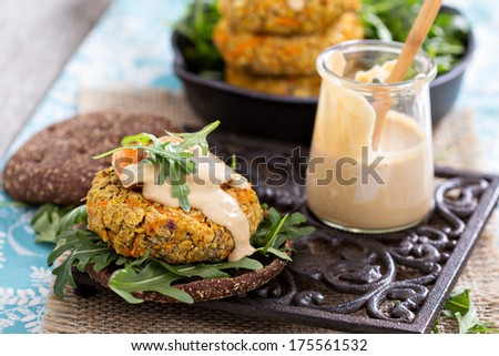 Vegan burgers with sweet potato served with arugula and peanut sauce - stock photo