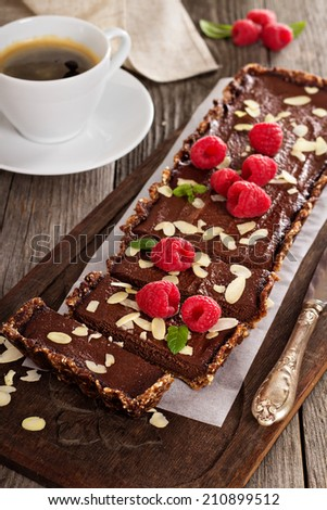 Vegan chocolate tart with almonds and a cup of coffee - stock photo