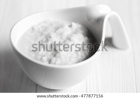 Vegan coconut milk rice porridge on white wooden table, copy space. Black and white