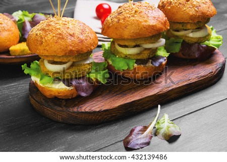 Vegan double burgers with vegetables, onion, vegetable cutlets, lettuce, sauce, ingredients for cooking vegan burgers cherry tomatoes, lettuce, rolls, skewers on wooden surface, dark black background - stock photo