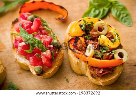 Vegan food: bruschetta with bell pepper, tomatoes, arugula, thyme and basil - stock photo