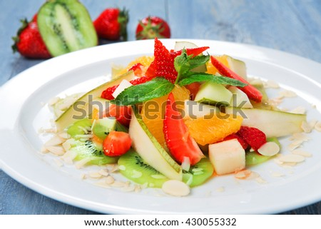 Vegan food. Vegetarian diet. Fruit salad at white plate. Fruit salad closeup. Healthy diet food, natural organic vegan salad with pear, strawberry, orange and almond slices.