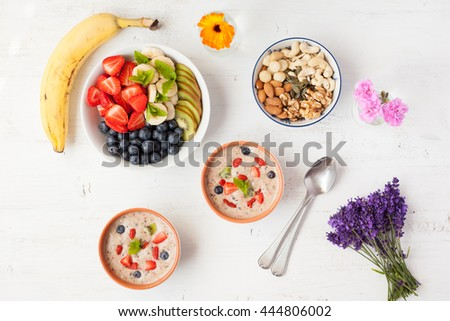 Vegan fruit and berry smoothie breakfast, topped with blueberries, strawberries and mint, top view, selective focus - stock photo
