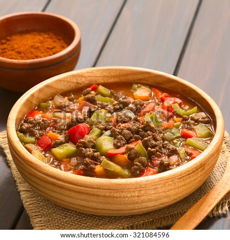 Vegan goulash made of soy meat (textured vegetable protein), capsicum, tomato and onion, served in wooden bowl, photographed with natural light (Selective Focus, Focus one third into the dish) - stock photo