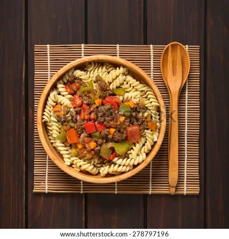 Vegan goulash made of soy meat (textured vegetable protein), capsicum, tomato, onion on fusilli pasta in wooden bowl, spoon and fork on side, photographed overhead on dark wood with natural light - stock photo