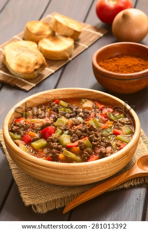 Vegan goulash made of soy meat (textured vegetable protein), capsicum, tomato, onion, served in wooden bowl, photographed with natural light (Selective Focus, Focus one third into the dish) - stock photo