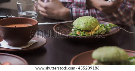 Vegan hamburger and cherry tomatoes are nice idea for vegan person. Vegan restaurant or cafe. Picture of vegan dish represented on plate. - stock photo