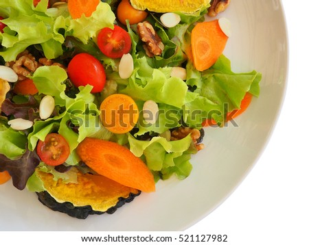 Vegan mix salad with almonds and walnuts on top on white background.