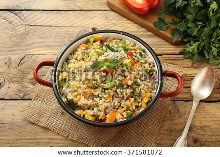 Vegan Quinoa salad in metal pan on rustic kitchen table background - stock photo