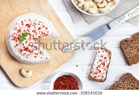 Vegan raw cheese from cashew nuts spread on the bread by knife on the white wooden background