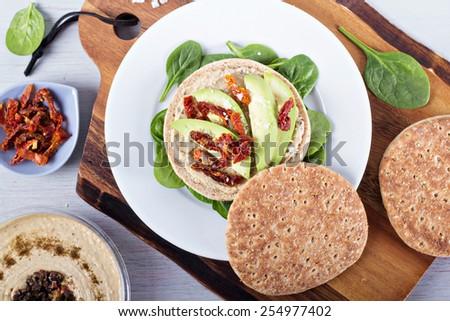 Vegan sandwich with hummus, avocado and dried tomatoes - stock photo
