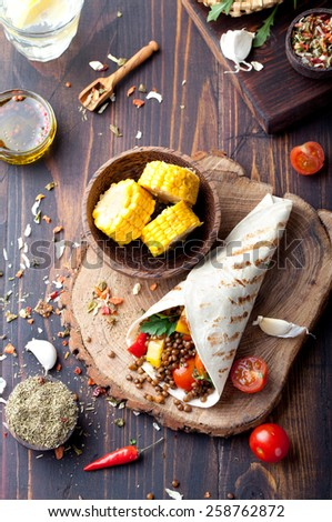 Vegan tortilla wrap, roll with grilled vegetables and lentil  and boiled corn cob on a wooden background - stock photo