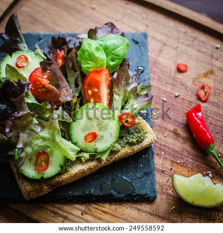 Vegan / vegetarian sandwich with green pesto and fresh vegetables. Selective focus. Top view - stock photo