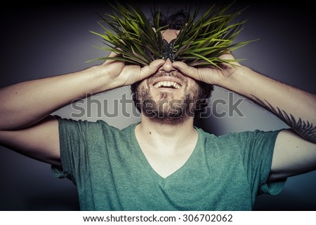 Veganism. ecology concept, man with green grass in the mouth - stock photo