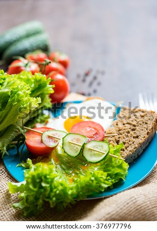 Vegetable and fried egg arrangement, cherry tomato's, sliced cucumber, salad leaves, wholegrain bread on a blue plate - stock photo
