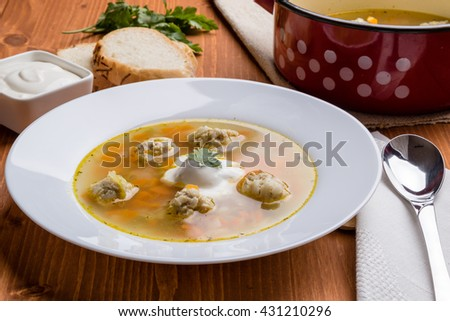 vegetable and meatball soup on wooden table in white plate