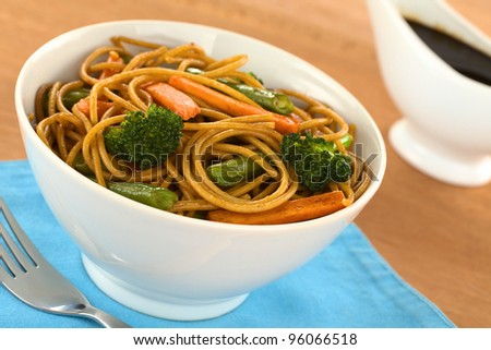 Vegetable and wholewheat spaghetti stir fry in white bowl with soy sauce in the back (Selective Focus, Focus on the broccoli floret on the left)