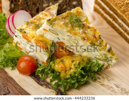 Vegetable carrot cheese and egg quiche pie. Vegetarian food served on a wooden plate with lettuce, sauce and tomatoes - stock photo