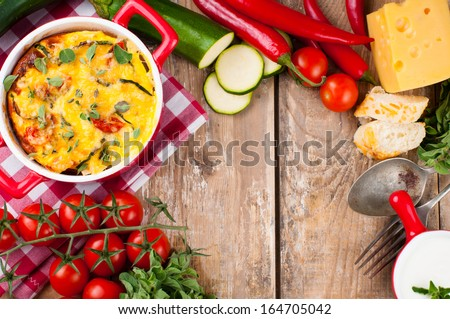 Vegetable casserole in a red pot with cheese, zucchini, cherry tomatoes, oregano and cream sauce on a wooden board, home cooking - stock photo