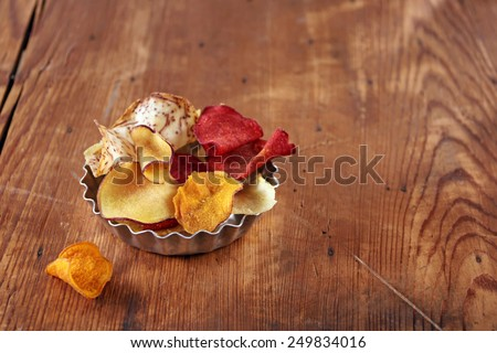 vegetable chips on wooden table - stock photo