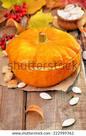 Vegetable cream soup in pumpkin and seeds on rustic wooden table