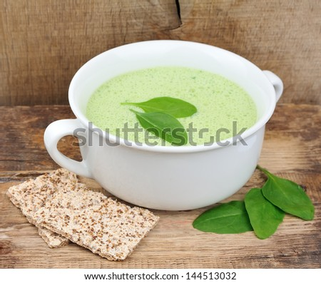 Vegetable cream soup with spinach on wooden tables. Dietary food. - stock photo