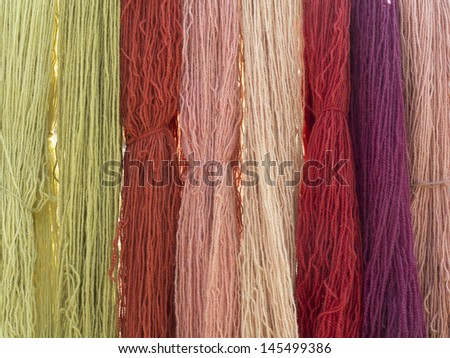 Vegetable dyed knitting wool seen on a medieval market. - stock photo