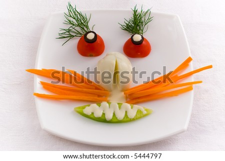 Vegetable face on a white plate - stock photo