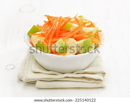 Vegetable fruit salad with carrots, apples, bananas in bowl on white wooden table - stock photo