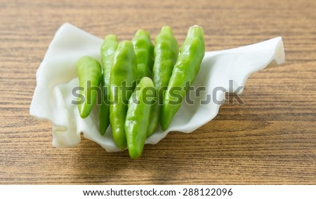 Vegetable, Green Chili or Chilli Cayenne Pepper on A White Cabbage Leaf. - stock photo