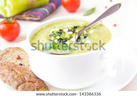 Vegetable green healthy cream soup with avocado, celery, zucchini and herbs in a white cup as an appetizer - stock photo